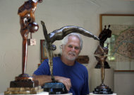 In this Thursday, Sept. 18, 2012 photo, Tony Dow, actor, director and artist, poses with, from left, Adam&#39;s Rib, Half Twist and Waiting, at his home and studio in the Topanga area of Los Angeles. When it comes time to sitting down in a studio and carving out bronze and wooden sculptures inspired by the nature all around him, Wally isn&#39;t leaving it up to the Beav these days. Dow, who famously played the Beaver&#39;s older brother Wally on the classic 1950s-60s sitcom &quot;Leave it To Beaver,&quot; is carving out a name for himself in the art world these days, as an abstract artist. (AP Photo/Reed Saxon)