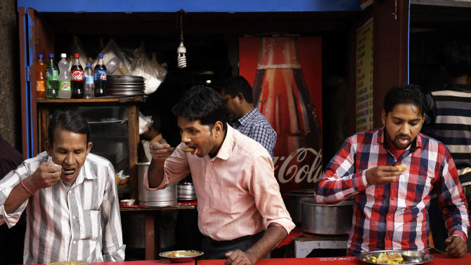 """In this Tuesday, Nov. 12, 2013 photo, Indians enjoy food spread out on a table by a road at a street food joint in New Delhi, India. Indian officials are conducting training seminars on the basics of food safety and hygiene, an attempt to curtail the infamous """"Delhi belly"""" that has struck down many an adventurous snacker in the country. (AP Photo/Saurabh Das)"""