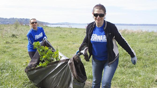 IMAGE DISTRIBUTED FOR CRUISE LINE INTERNATIONAL ASSOCIATION -  Windstar Cruises employee Kathy Anderson, left, and Toni Vasileva drag a tarp full of invasive species, including blackberry plants, Japanese Knotweed and Scotch Broom, from the dunes during Seattle Cruise Industry Employee Volunteer Day, on Tuesday, April 23, 2013 at Golden Gardens Park in Seattle. Holland America Line, Seabourn, Windstar Cruises, Paul Gauguin Cruises, the Port of Seattle and Seattle Parks and Recreation all joined together as part of the Cruise Forward Initiative (www.cruiseforward.org) to participate in dune restoration efforts, in celebration of Earth Day and National Volunteer Week. (Stephen Brashear/AP Images for Cruise Line International Association)