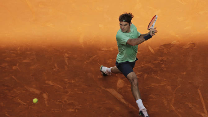 Roger Federer from Switzerland returns the ball during the match against Kei Nishikori from Japan at the Madrid Open tennis tournament, in Madrid, Thursday, May 9, 2013. (AP Photo/Andres Kudacki)