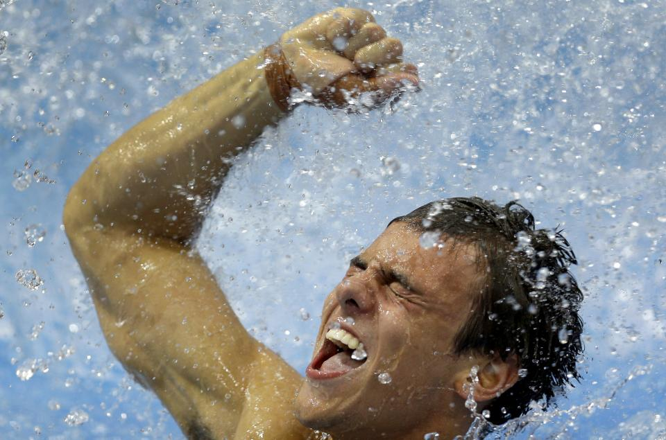 Bronze medalist Thomas Daley from Britain celebrates after the men's 10-meter platform diving final at the Aquatics Centre in the Olympic Park during the 2012 Summer Olympics in London, Saturday, Aug. 11, 2012. (AP Photo/Michael Sohn)
