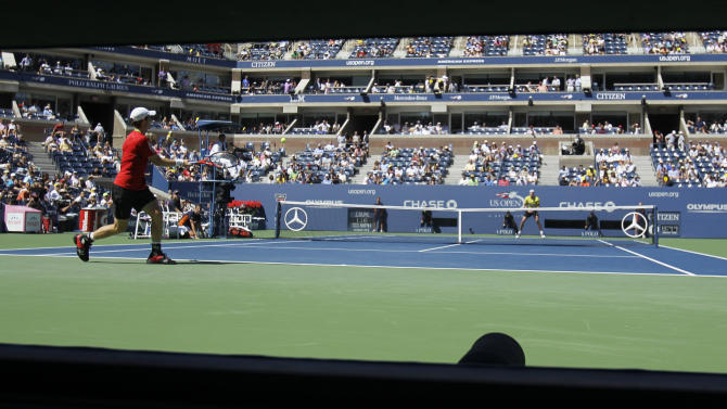Andy Murray of Britain serves to John Isner during a quarterfinal match at the U.S. Open tennis tournament in New York, Friday, Sept. 9, 2011. (AP Photo/Mike Groll)