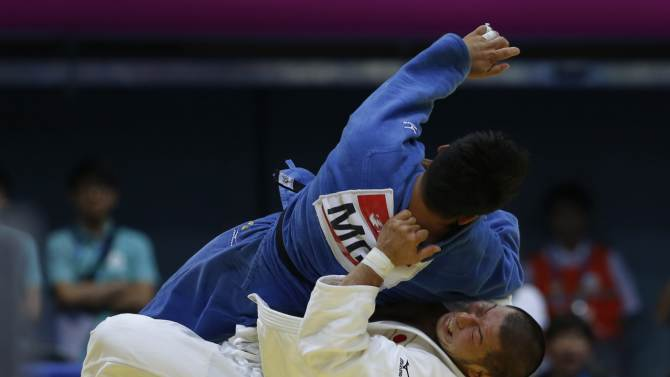 Japan's Yusuke Kumashiro competes with Mongolia's Tuvshinbayar Naidan during their men's team bronze medal judo contest at Dowon Gymnasium during the 17th Asian Games in Incheon