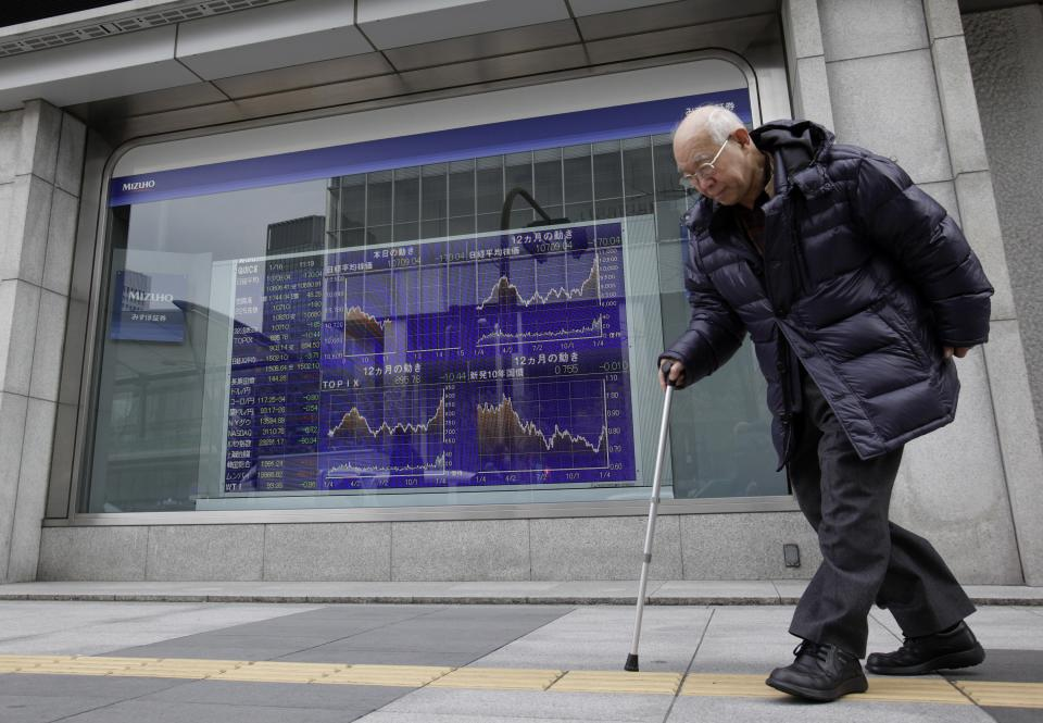 A man walks past an electric stock price indicator in Tokyo, Wednesday, Jan. 16, 2013. Japan's benchmark index toppled off a 32-month high Wednesday after its currency's downward slide went into reverse. (AP Photo/Shizuo Kambayashi)