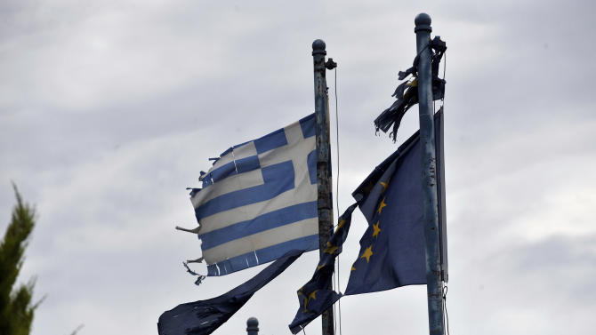 In this Friday, May 25, 2012 photo torn EU and Greek flags fly at the entrance of an abandoned factory in the industrial zone of Komotini about 800 kilometers (500 miles) northeast of Athens. In its heyday just over a decade ago, the industrial zone in this far-flung area of northern Greece was a hive of activity, with dozens of factories producing everything from textiles to ceramics and employing nearly 20,000 people. Now, the Komotini industrial zone is a picture of desolation, a stark illustration of the toll Greece's vicious financial crisis has taken on the country's industry. (AP Photo/Nikolas Giakoumidis)
