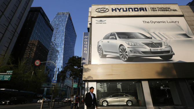 A man crosses a road in front of a Hyundai dealership in downtown Seoul, South Korea, Wednesday, April 24, 2013. (AP Photo/Kin Cheung)