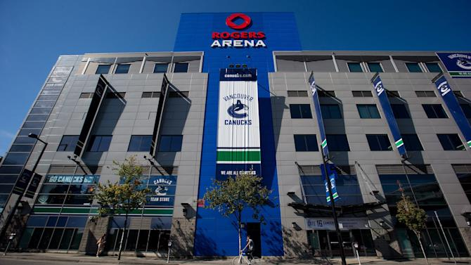 A cyclist rides past Rogers Arena, the home of the Vancouver Canucks NHL hockey team, in Vancouver, British Columbia, on Sunday Sept. 16, 2012. The NHL locked out its players at midnight Saturday, the fourth shutdown for the NHL since 1992, including a year-long dispute that forced the cancellation of the entire 2004-05 season. (AP Photo/The Canadian Press, Darryl Dyck)