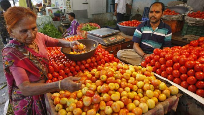A woman buys tomatoes at a wholesale vegetable market in the western Indian city of Ahmedabad