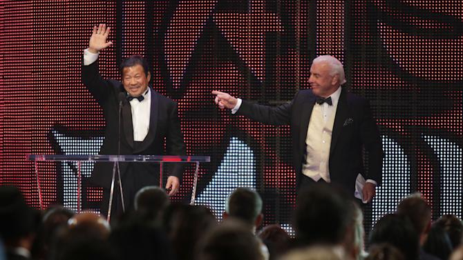 IMAGE DISTRIBUTED FOR WWE - Inductee Tatsumi Fujinami, left, is introduced by Ric Flair at the WWE Hall of Fame Ceremony, on Saturday, March 28, 2015 in San Jose, Calif. Nine inductees were honored in the class of 2015, including actor and former California Governor Arnold Schwarzenegger. (Don Feria/AP Images for WWE)