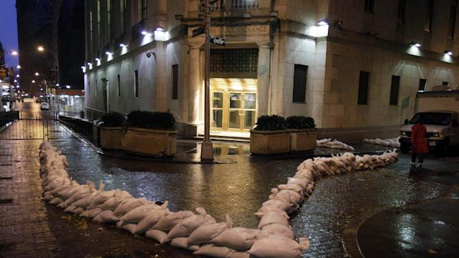 Sandbags protect an entrance of the New York Stock Exchange, Monday, Oct. 29, 2012. Hurricane Sandy continued on its path Monday, forcing the shutdown of mass transit, schools and financial markets, sending coastal residents fleeing, and threatening a dangerous mix of high winds and soaking rain. There had been plans to allow electronic trading to go forward on the New York Stock Exchange but with a storm surge expected to cover parts of lower Manhattan in water, officials decided late Sunday that it was too risky to ask any personnel to staff the exchanges. (AP Photo/Richard Drew)