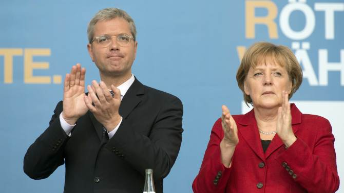 German Chancellor Angela Merkel, right, attends an election campaign rally together with Norbert Roettgen, left, top candidate of the Christian Democratic Union party CDU for the North-Rhine Westphalian federal state elections in Gelsenkirchen, Germany, Wednesday, May 9, 2012. Germany's most populous federal state will go to the polls next Sunday. (AP Photo/Martin Meissner)
