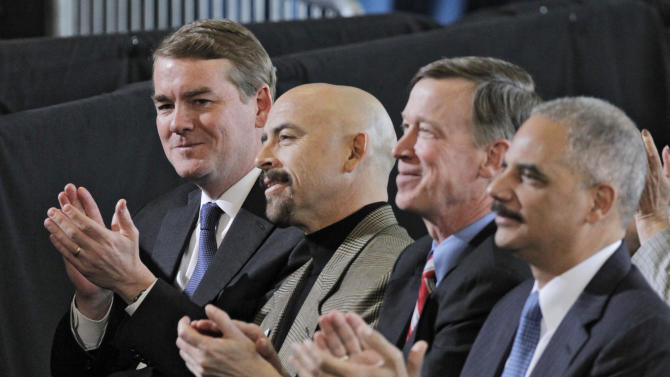 U.S. Senator Michael Bennet, left, Colorado Lt. Gov. Joe Garcia, Gov. John Hickenlooper and U.S. Attorney General Eric Holder applaud President Barack Obama during his speech on gun control at the Denver Police Academy on Wednesday, April 3, 2013. Obama met with local law enforcement officials and community leaders to discuss the state's new measures to reduce gun violence.(AP Photo/Ed Andrieski)