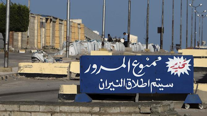 A sign outside the security headquarters warns vehicles not to proceed or they will be shot, in el-Arish, 290 kilometers (180 miles) east of Cairo, North Sinai, Egypt, Saturday, Jan. 31, 2015. Egyptian President Abdel Fattah al-Sissi told the nation in a televised address Saturday to prepare for a long fight to defeat Islamic extremists following a wave of attacks on security forces in the Sinai Peninsula. An Islamic State-linked group in Egypt claimed responsibility for a string of bomb and gun attacks Thursday night targeting Egyptian military positions that killed at least 30 security force members. (AP Photo)