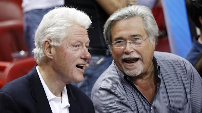 Former President Bill Clinton, left, chats with Miami Heat owner Micky Arison as they sit courtside before an NBA basketball game between the Heat and the Orlando Magic, Sunday, Feb. 19, 2012, in Miami. (AP Photo/Wilfredo Lee)