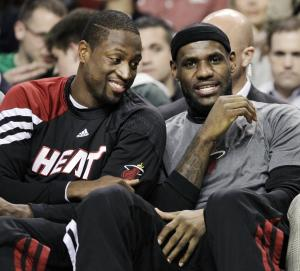 Miami Heat's Dwyane Wade, left, and LeBron James chat on the bench during the first minutes of an NBA basketball game against the Boston Celtics in Boston, Tuesday, April 24, 2012. (AP Photo/Elise Amendola)