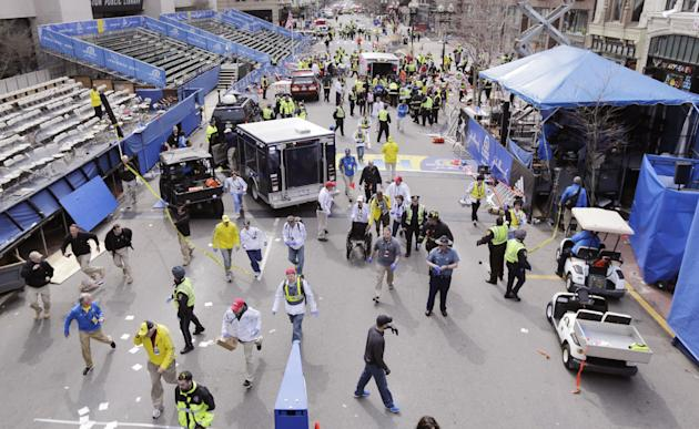 Police clear the area at the finish line of the 2013 Boston Marathon following an explosion in Boston, Monday, April 15, 2013.   Two explosions shattered the euphoria of the Boston Marathon finish lin