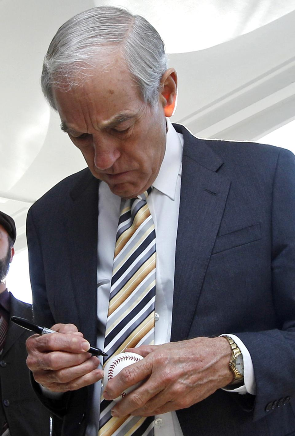 Republican presidential candidate Rep. Ron Paul, R-Texas, signs an autograph on a baseball while campaigning in Exeter, N.H., Tuesday Dec. 20, 2011. (AP Photo/Charles Krupa)