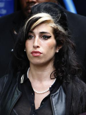"FILE - In this July 24, 2009 file photo, British singer Amy Winehouse leaves Westminster magistrates court in London after a judge acquitted her of assaulting a fan who asked to take her picture. Winehouse had no illegal drugs in her system when she died, and it is still unclear what killed the singer, her family said Tuesday, Aug. 23, 2011. The family said in a statement that toxicology tests showed ""alcohol was present"" in the singer's body but it hasn't yet been determined if it contributed to her death. (AP Photo/Kirsty Wigglesworth)"