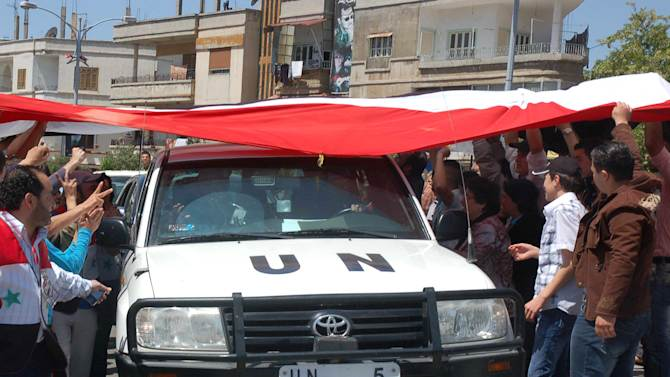 In this photo released by the Syrian official news agency SANA, a UN observers vehicle passes under a huge Syrian flag held by Syrian President Bashar Assad supporters during their visit to the pro-Syrian regime neighborhoods, in Homs province, central Syria, on Monday April 23, 2012. United Nations observers monitoring Syria's shaky cease-fire visited a string of rebellious Damascus suburbs Monday, while the European Union looked set to levy new sanctions to increase the pressure on President Bashar Assad's regime. (AP Photo/SANA)