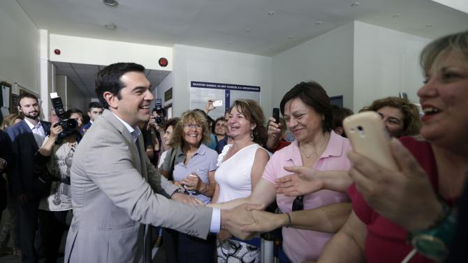 Greece's Prime Minister Alexis Tsipras, left, shakes hands with employees during his visit at the Education Ministry in Athens, Tuesday, June 2, 2015. Tsipras says Greece has submitted a proposal for an agreement with its creditors, as Athens seeks a deal that will to unlock desperately needed rescue money. (AP Photo/Thanassis Stavrakis)