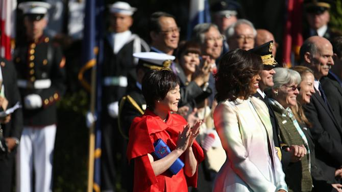First lady Michelle Obama and  Japanese Prime Minister Shinzo Abe's wife Akie Abe, stand with dignitaries as President Barack Obama hosts a state arrival ceremony for the Japanese prime minister, Tuesday, April 28, 2015, on the South Lawn of the White House in Washington. (AP Photo/Andrew Harnik)