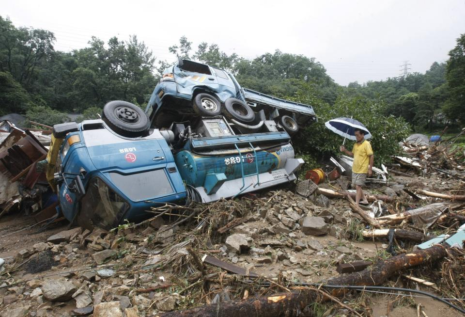 A South Korean man walks by wrecked vehicles after a landslide in Seoul, South Korea, Wednesday, July 27, 2011. A quick blast of heavy rain sent landslides barreling through South Korea's capital and a northern town Wednesday. (AP Photo/Ahn Young-joon)