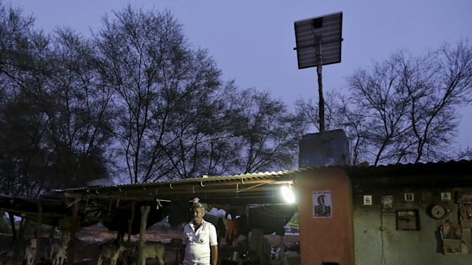 Villager Mohan Bharwad poses next to a Compact Fluorescent Lamp (CFL) powered by solar energy, outside his house on the outskirts of Gandhinagar