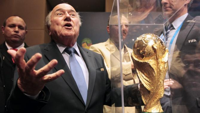 FIFA President Sepp Blatter gestures next to the World Cup trophy after a media conference in Sao Paulo