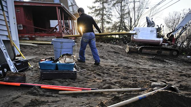 In this Dec. 4, 2012, photo, Reginaldo Ferreira of Russe Builders carries wood to construct a wall to protect a beachfront home in Fairfield, Conn. The national economy is expected to absorb the blow from Sandy with little long-term damage, but in the short term, at least, Sandy is introducing dramatic booms and busts across the Northeast. The effects vary widely across industries, bringing banner years for some while pushing others toward economic ruin. (AP Photo/Jessica Hill)