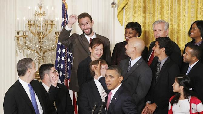 FILE This Sept. 23, 2011 file photo shows John Becker, a fourth grade teacher from DC Prep Public Charter School in Washington, D.C., top row center, reacting after he was acknowledged by President Barack Obama as he stands with educators and students as he speaks about No Child Left Behind Reform in the East Room at the White House in Washington. States and local governments have the primary responsibility for education in the United States. But the federal government gets a big say, too, by awarding billions in aid that often has strings attached.   (AP Photo/Charles Dharapak, File)