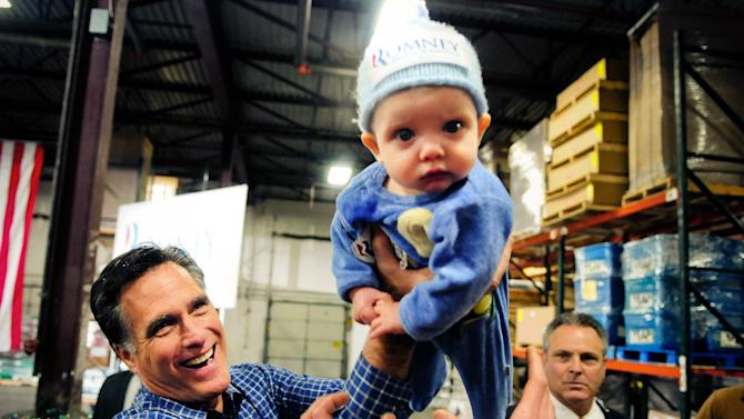 """Republican presidential candidate Mitt Romney  left, hands 6-month-old Dexter Hall of Plymouth, Minn. back to his mother, Laura, during a campaign stop at Freightmasters, Inc. in Eagan, Minn., on Wednesday, Feb.  1, 2012.  Romney, who won big in Florida with a barrage of negative ads, predicted the tone of the GOP campaign was """"just a precursor to what you'll see"""" from President Barack Obama in the general election. And he said voters paid more attention to what they heard in the campaign debates than whatever ads were flooding the airwaves.  (AP Photo/The St. Paul Pioneer Press, Ben Garvin )  MINNEAPOLIS STAR TRIBUNE OUT"""