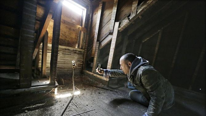 """In an April 3, 2013 photo, Tony Majka, who is also known as Tony Detroit on Instagram, uses his iPhone to photograph inside an abandoned home in Detroit. Majka has been chronicling Detroit's blight epidemic in a unique and popular way. Under the name """"Tony Detroit,"""" he's been taking photos of the city's many abandoned structures with an iPhone and posting them on Instagram. The simple shots of Detroit's desolation has earned him better than 300,000 followers. (AP Photo/Carlos Osorio)"""