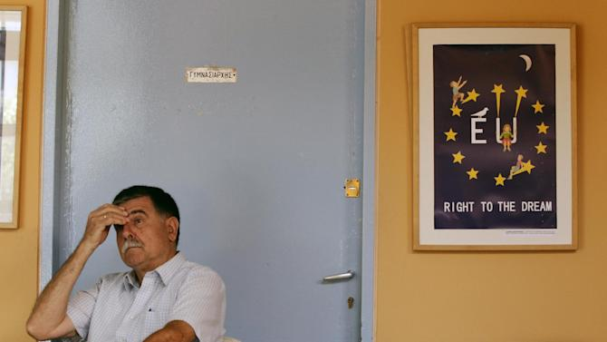 A man sits as he waits to vote at a polling station in Athens, Sunday, July 5, 2015. Greeks began voting early Sunday in a closely-watched, closely-contested referendum, which the government pits as a choice over whether to defy the country's creditors and push for better repayment terms or essentially accept their terms, but which the opposition and many of the creditors paint as a choice between staying in the euro or leaving it. (AP Photo/Thanassis Stavrakis)
