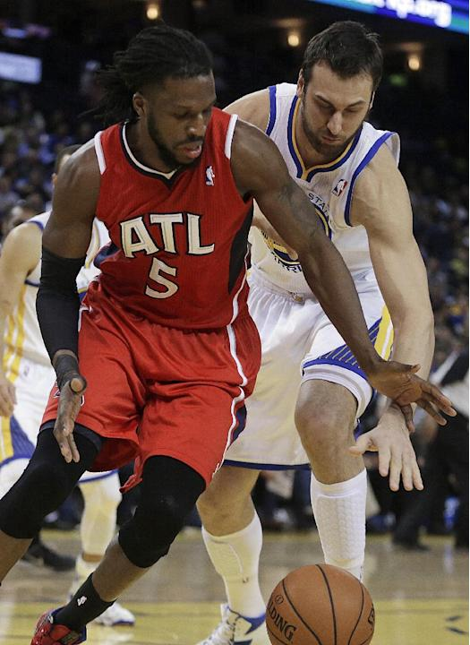 Atlanta Hawks' DeMarre Carroll (5) and Golden State Warriors' Andrew Bogut chase a loose ball during the first half of an NBA basketball game Friday, March 7, 2014, in Oakland, Calif