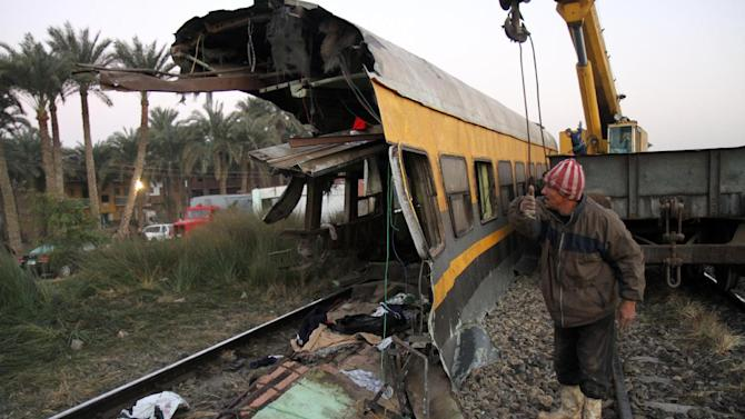 Egyptians railway workers attempt to remove debris from tracks following a train crash in Badrasheen, 40 KM south of Cairo, Egypt, Tuesday, Jan. 15, 2013. At least 19 people died and more than 100 were injured when two railroad passenger cars derailed just south of Cairo, health officials say. The accident comes less than two weeks after a new transportation minister was appointed to overhaul the rail system, and just two months after a deadly collision between a train and school bus. (AP Photo/Ahmed Gomaa)