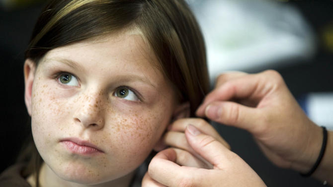 FILE -This May 2010 file photo shows Zahra Clare Baker, 10, getting a hearing aid during an event at Charlotte Motor Speedway in Hickory, N.C. Elisa Baker, Zahra's mother, was indicted in January 2011 on a bigamy charge involving her marriage to Adam Baker, Zahra Clare Baker's father, and another man, but AP found documents at a half a dozen county courthouses that showed at one point she was married to three men at the same time, calling into question the single charge. The question of bigamy is unrelated to the Zahra Clare Baker case. (AP Photo/The Independent Tribune, James Nix, File)