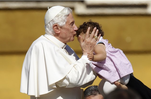 Pope Benedict XVI kisses a baby at the end of his weekly audience in Saint Peter's Square at the Vatican