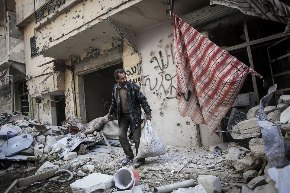 In this Sunday, Dec. 2, 2012 photo, a man collects his belongings after his home was damaged due to heavy fighting between Free Syrian Army fighters and government forces in Aleppo, Syria. (AP Photo/Narciso Contreras)