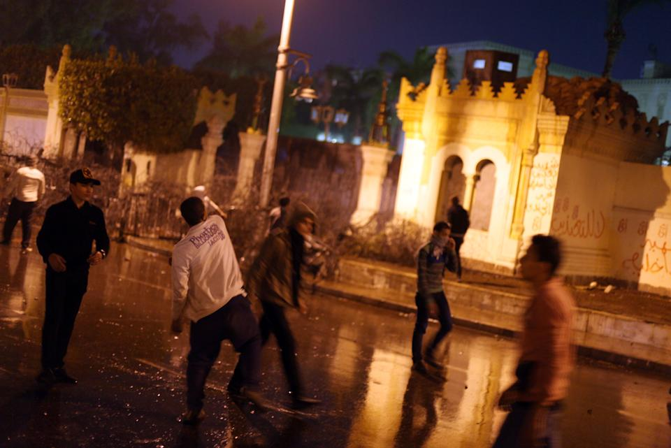 Egyptian protesters throw stones at the presidential palace during a demonstration in Cairo, Egypt, Monday, Feb. 11, 2013. Security forces sprayed protesters with water hoses and tear gas outside the presidential palace Monday as Egyptians marked the second anniversary of autocrat Hosni Mubarak's ouster with angry demonstrations against his elected successor.(AP Photo/Khalil Hamra)