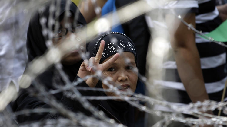 A Filipino Muslims woman flashes the peace sign behind a barb wired fence as they gather in support of a preliminary peace agreement between the government and  the nation's largest Muslim rebel group during a rally outside the gates of the Malacanang presidential palace in Manila, Philippines on Monday Oct. 15, 2012. Worn down by decades of fighting and failed peace agreements, about 200 Muslim rebels were euphoric but cautious before they sign a peace pact Monday with the Philippine government aimed at ending one of Asia's longest-running insurgencies. (AP Photo/Aaron Favila)