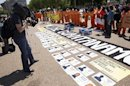 A cameraman films activists wearing orange jumpsuits as they mark the 100th day of prisoners' hunger strike at Guantanamo Bay during a protest in front of the White House in Washington