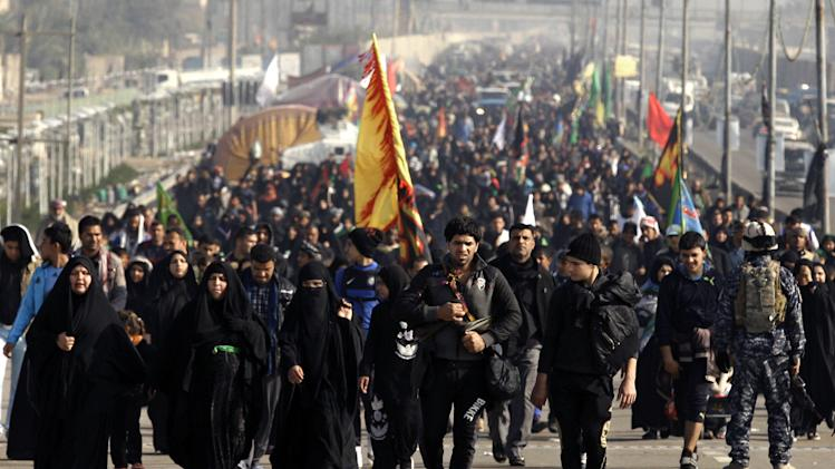 Shiite pilgrims march to Karbala for Arbaeen in Baghdad, Sunday, Dec. 30, 2012. The holiday marks the end of the forty day mourning period after the anniversary of the 7th century martyrdom of Imam Hussein the Prophet Muhammad's grandson. (AP Photo/Hadi Mizban)