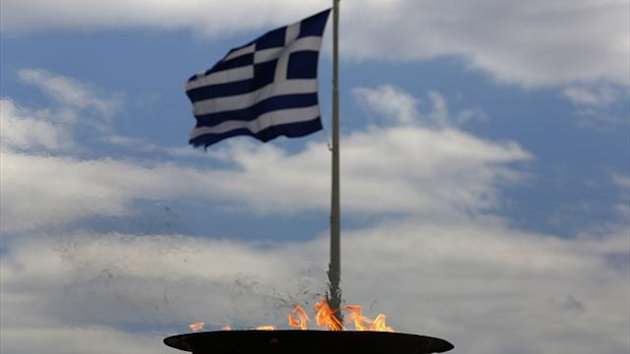 A Greek flag flutters next to a cauldron with the Olympic Flame atop the Athens Acropolis May 17, 2012.