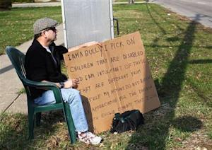 """Aviv sits with an """"I am a bully"""" sign at a street corner in the Cleveland suburb of South Euclid"""