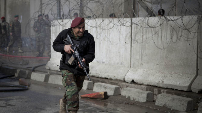 An Afghan Army soldier runs outside the Afghan Defense Ministry after a suicide bomber on a bicycle struck outside the ministry, killing at least nine Afghan civilians as U.S. Defense Secretary Chuck Hagel visited Kabul, Afghanistan, Saturday, March 9, 2013.  (AP Photo/Anja Niedringhaus)