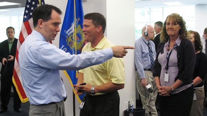 Wisconsin Gov. Scott Walker greets employees of Total Administrative Services Corp., on Monday, May 21, 2012, in Madison, Wis. Walker, who faces a recall election in two weeks, is up in the polls and appears to have the momentum in the race.  (AP Photo/Scott Bauer)