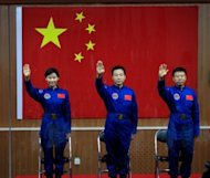 <p>Chinese first woman astronaut Liu Yang together with her two male colleagues, Jing Haipeng (centre) and Liu Wang wave as they are introduced during a press conference at the Jiuquan space base in Gansu province. China launched its most ambitious space mission to date, sending its first female astronaut to the final frontier and bidding to achieve the country's first manual space docking.</p>