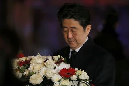 Japan's Prime Minister Shinzo Abe carries a bouquet of flowers as he arrives at the Bataclan conert hall to pay tribute to the victims of the shooting attacks in Paris