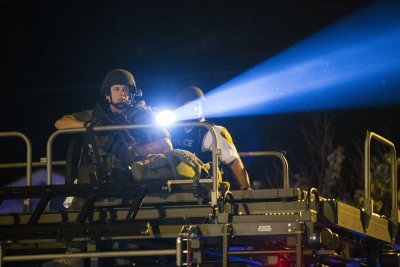 CLICK IMAGE for slideshow: A police officer points a spotlight at a more vocal and confrontational group of demonstrators during further protests in r...