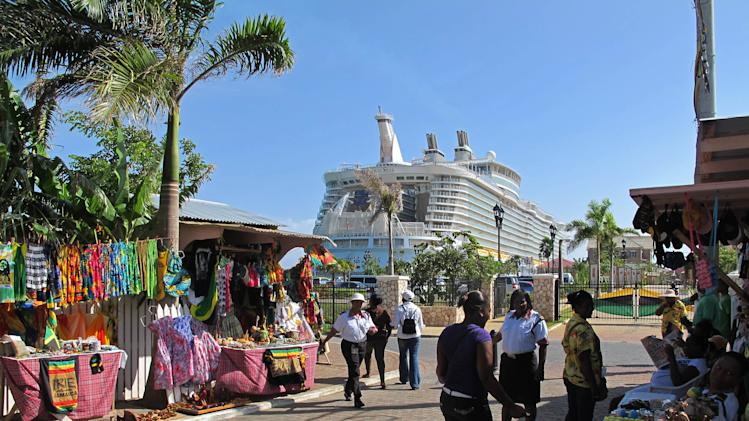 In this Sept. 26, 2012 photo, the Royal Caribbean's Allure of the Seas cruise ship is docked in Falmouth, northern Jamaica as street vendors sell clothes, souvenirs and other goods to tourists. Trade groups say the flourishing cruise ship industry injects about $2 billion a year into the economies of the Caribbean, the world's No. 1 cruise destination, but critics complain that it produces relatively little local revenue because so many passengers dine, shop and purchase heavily marked-up shore excursions on the boats or splurge at international chain shops on the piers.  (AP Photo/David McFadden)